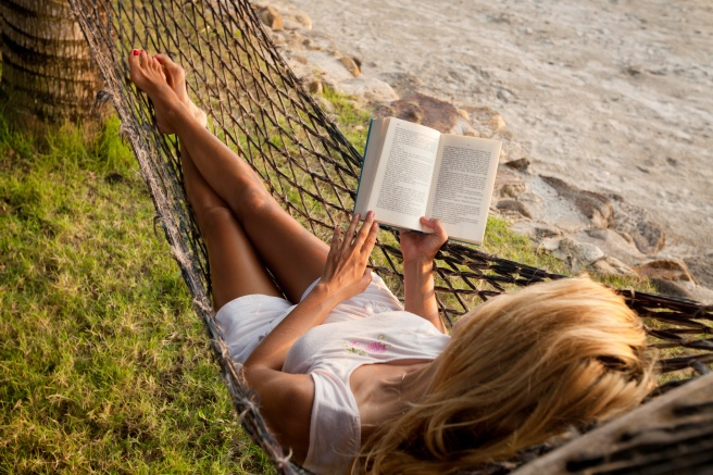 Woman reading in a hammock on the beach